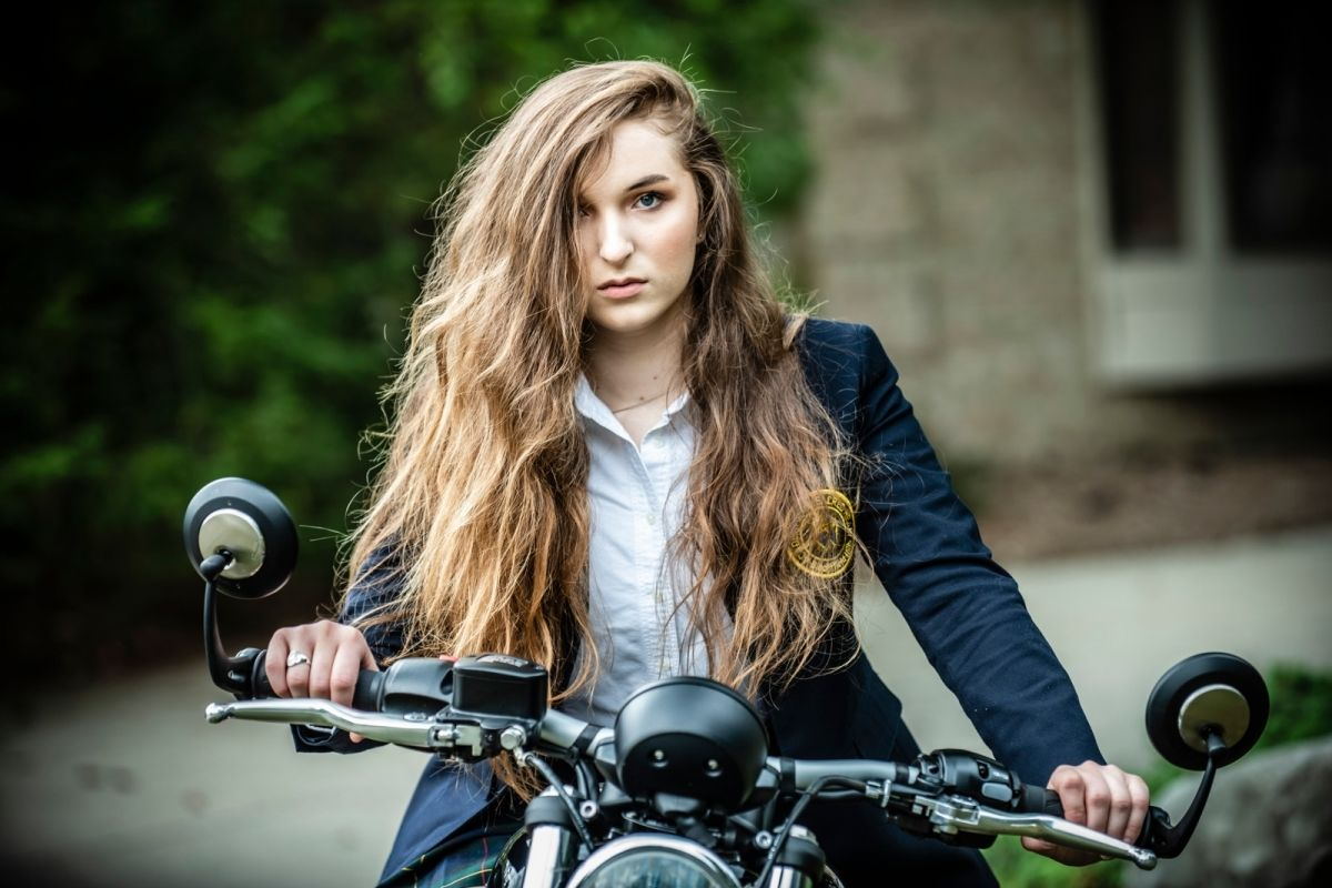 girl with long curly brown hair on motorcycle